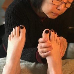 woman in black touching feet Reflexology Healing Medfield MA